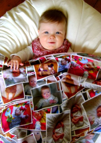 baby under blanket with photos