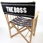 "Chair with filmstrip printed seat and ""the boss"" written on back"