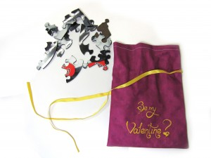 Purple pouch with yellow ribbon and text and pices of jigsaw puzzle