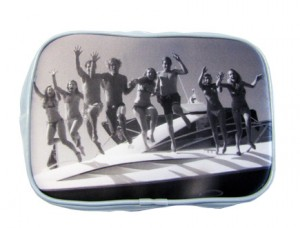 Teenagers jumping off boat in black and white on a blue make-up bag