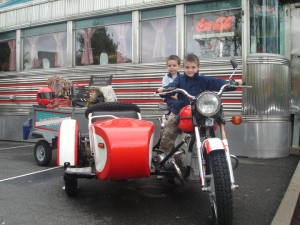 Two boys on a moped in front of a diner