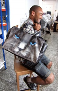 Man sitting on a chair holding a holdall with a cat printed on it