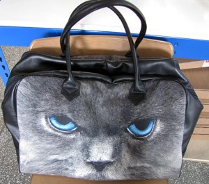 Leather holdall with cat's face sitting on a chair
