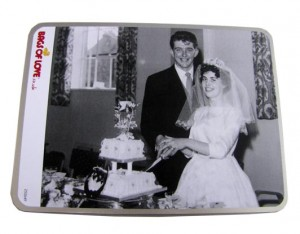 wedding photo of a couple cutting a cake in black and white on a tin box