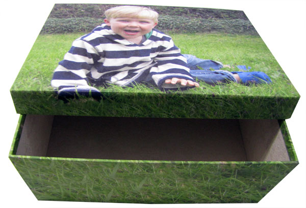 Child lying on the grass on an open photo box