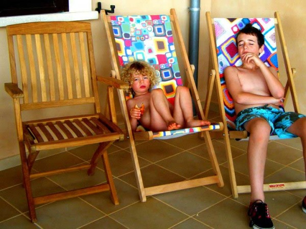 Two boys sitting on two colourful deckchairs