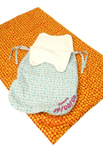 Orange blanket and a blue baby sleeping bag with pink text