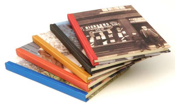 Five notebooks stacked on top of each other with photos on the covers