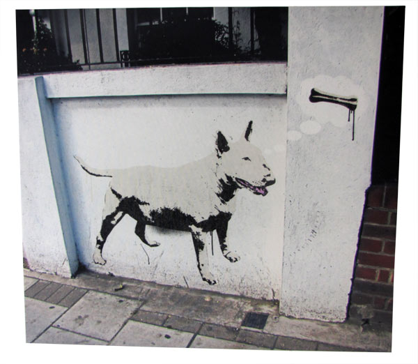 Dog painted on a white wall in the street