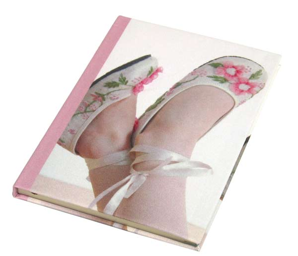 A little girls feet on the cover of a diary