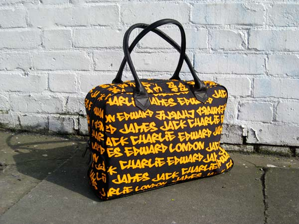 Black holdall with yellow graffiti text standing next to a white brick wall
