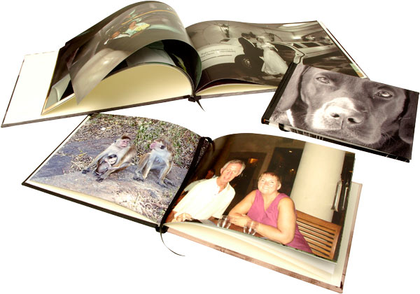 Two open and one closed photo books displaying photos
