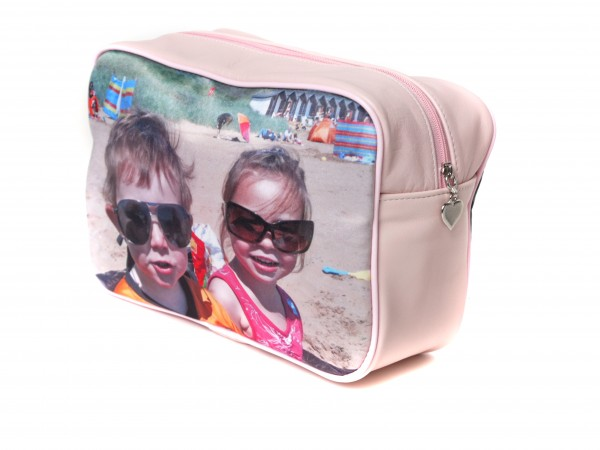 Two kids on the beach wearing sunglasses on a pink washbag