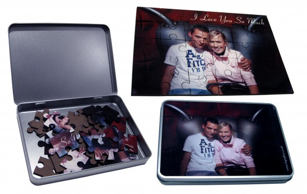 Open tin box with puzzle pieces inside, a finished photo puzzle and the cover of the tin box