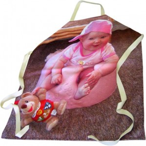 Baby in pink clothes sitting on a pink cushion on an apron