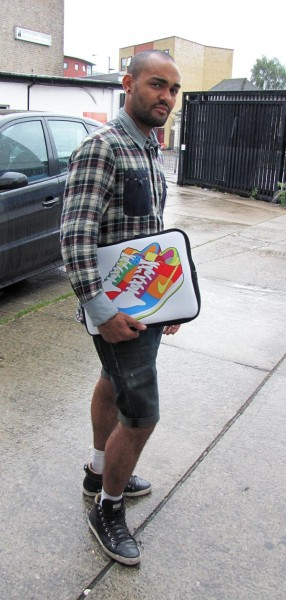 Man holding a laptop bag with cartoon trainers