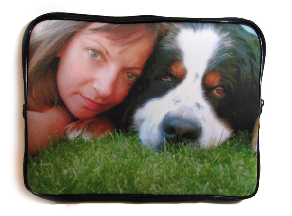 Woman and dog lying on the grass on the cover of a laptop bag