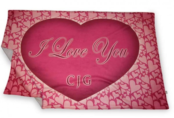 One large pink heart with text in it on a blanket with a small hearts pattern