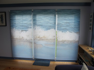 Three roller blinds on large windows with an ocean image