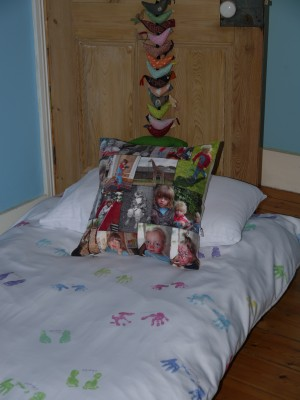 Bed with hand and foot prints duvet cover and photo montage cushion