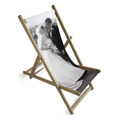 A couple on their wedding day on the seat of a deckchair