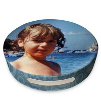 Boy standing next to the oceaon on a round cushion