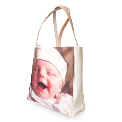 Smiling baby on the cover of a beige shopper bag