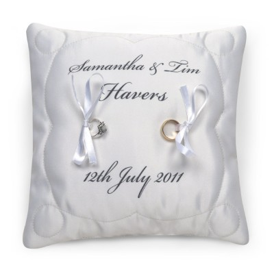 White cushion with black text and two wedding rings on it