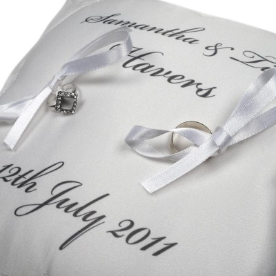 Two wedding rings, ribbons and text on a white cushion