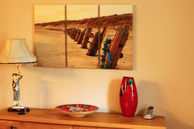 A triptych canvas print of a sandy beach above a shelf