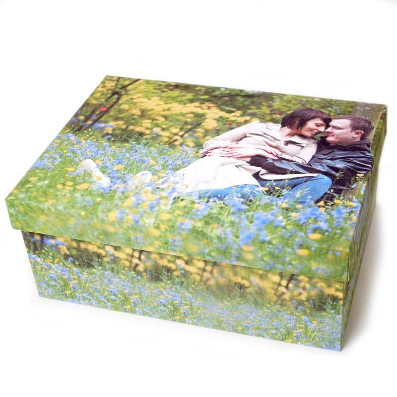 photo storage box of a married couple sitting in a meadow surrounded by beautiful flowers